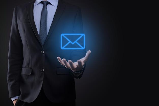 電子メールアイコンを持っているビジネスマンの手、ニュースレターの電子メールで私達に連絡し、スパムメールからあなたの個人情報を保護します。カスタマーサービスコールセンターお問い合わせコンセプト。