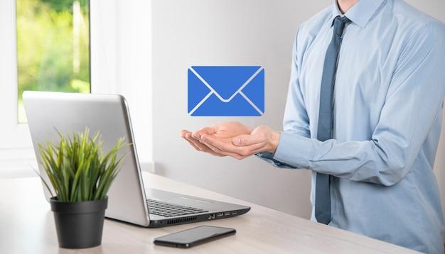 사업가가 이메일 아이콘을 들고 뉴스레터 이메일로 연락하고 스팸 메일로부터 개인 정보를 보호합니다. 고객 서비스 콜 센터 문의 개념입니다.