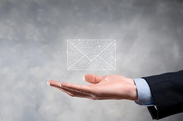 電子メールアイコンを持っているビジネスマンの手、ニュースレターの電子メールでお問い合わせ、スパムメールからあなたの個人情報を保護します