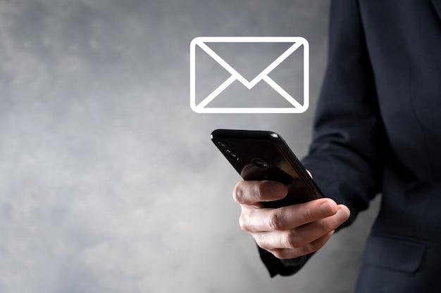 사업가 손을 잡고 전자 메일 아이콘, 뉴스 레터 이메일로 문의하고 스팸 메일로부터 개인 정보를 보호하십시오.