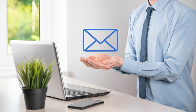Businessman hand holding e-mail icon, contact us by newsletter email and protect your personal information from spam mail. customer service call center contact us concept