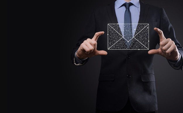 Businessman hand holding e-mail icon, contact us by newsletter email and protect your personal information from spam mail. customer service call center contact us concept.