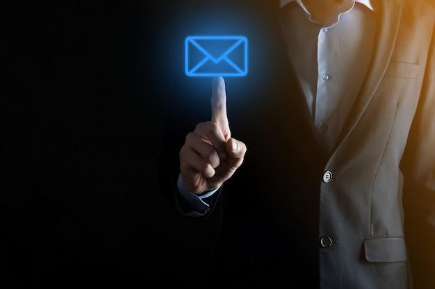 電子メールアイコンを持っているビジネスマンの手