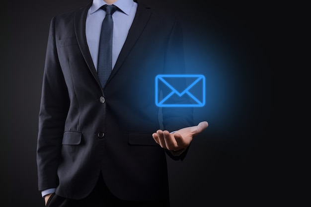電子メールのアイコンを持っているビジネスマンの手