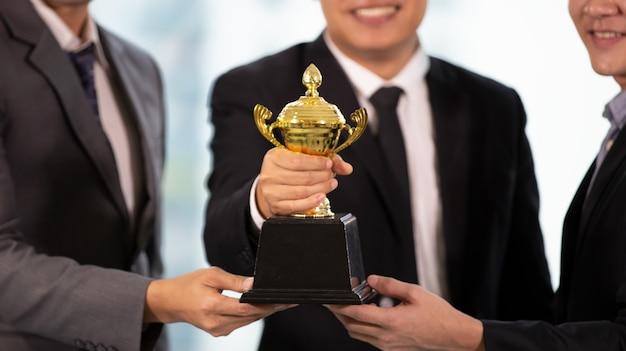 金のトロフィーを持っているビジネスマンの手、ビジネスの勝者賞。