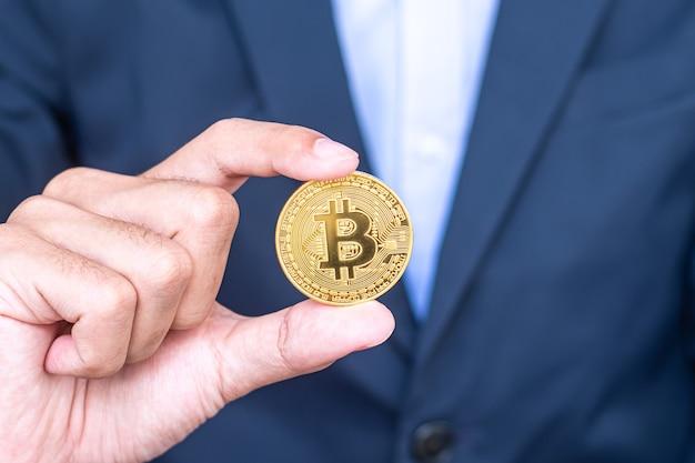 Рука бизнесмена, держащая золотую криптовалюту bitcoin (btc), crypto - это цифровые деньги в сети блокчейнов, обмен осуществляется с помощью технологий и онлайн-обмена. финансовая концепция