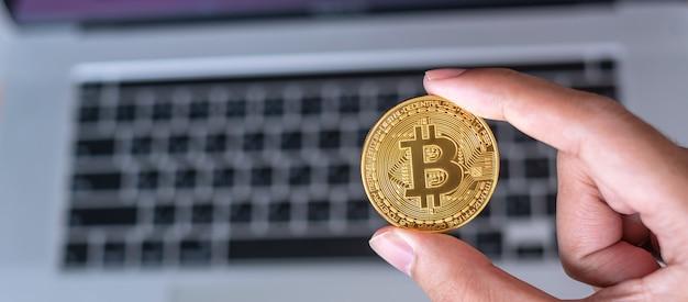 Рука бизнесмена, держащая золотую криптовалюту bitcoin (btc) над клавиатурой ноутбука, crypto - это цифровые деньги в сети блокчейн, обмен осуществляется с использованием технологий и концепции онлайн-обмена