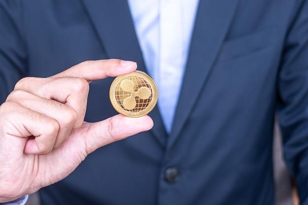 사업가가 황금 리플(xrp) 암호화폐 코인을 들고 있는 크립토는 블록체인 네트워크 내에서 디지털 머니이며 기술과 온라인 인터넷 교환을 사용하여 교환됩니다. 금융 개념