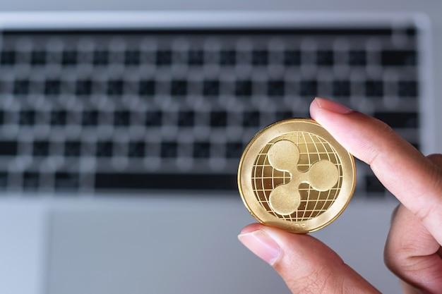 Рука бизнесмена держащая золотую монету криптовалюты ripple (xrp) над клавиатурой ноутбука, монета ripple. крипто - это цифровые деньги в сети блокчейнов.