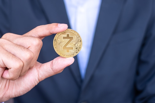 Рука бизнесмена, держащая золотую криптовалютную монету zcash (zec), crypto - это цифровые деньги в сети блокчейн, обмен осуществляется с помощью технологий и онлайн-обмена в интернете. финансовая концепция