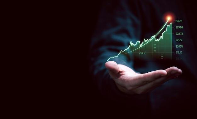 Рука бизнесмена держащая увеличивающийся виртуальный инвестиционный график и диаграмму для тенденции анализа фондового рынка и технической концепции трейдера.