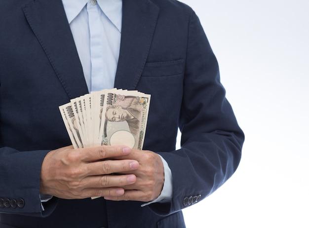 日本の紙幣を持っているビジネスマンの手
