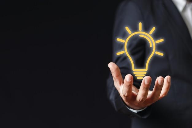 電球のアイコンを持っているビジネスマンの手。インスピレーションを学ぶアイデア。考えて創造的なコンセプト。