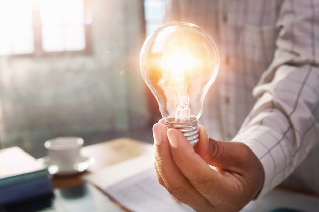Businessman hand holding light bulb in office.