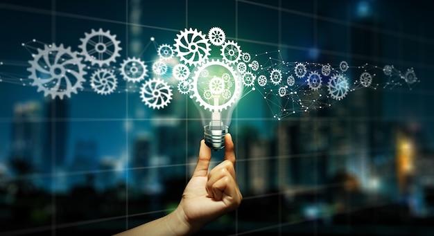 中に歯車と電球を持っているビジネスマンの手。クリエイティブとインスピレーションとのビジネスアイデア電球ギアアイコンネットワーク接続。イノベーション、リーダーシップ、チームワーク、アイデア、ビジョン、計画コンセプト。