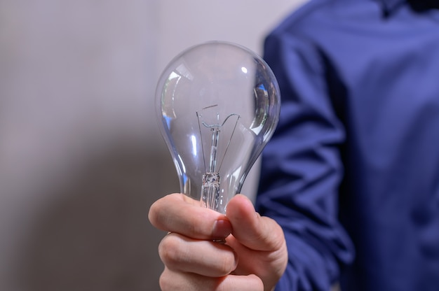 Businessman hand holding a light bulb
