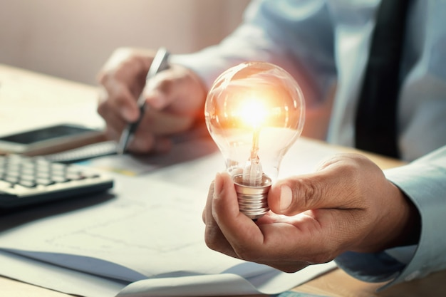 Businessman hand holding lightbulb in office.
