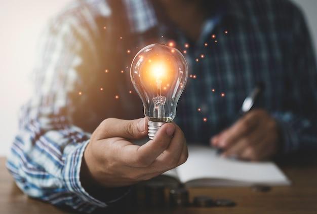 실업가 손을 잡고 오렌지 빛나는 및 연결 선으로 전구. 창의적 사고 아이디어 개념입니다.