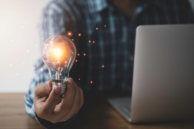 Businessman hand holding lightbulb with orange glowing and creative idea to laptop.