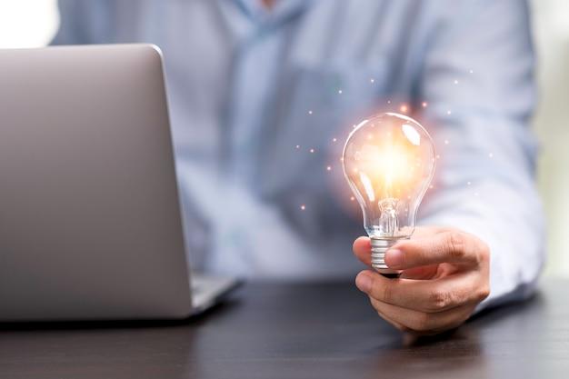 Рука бизнесмена держа лампочку с оранжевым светом для концепции идеи творческого мышления.