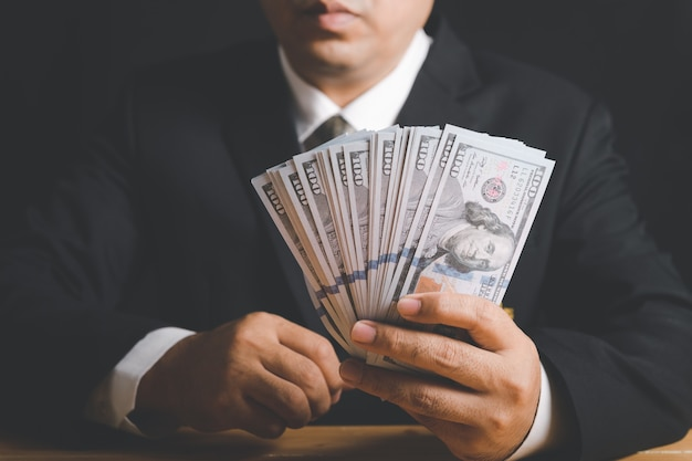 사업가 손을 잡고 돈을-미국 달러. 투자, 성공 및 수익성있는 비즈니스 개념