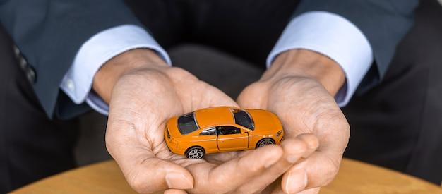 사업가 손을 테이블에 주황색 자동차 장난감을 잡고