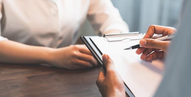 Рука бизнесмена удерживая ручку кладя на бумагу и проект контракта с клиентами.