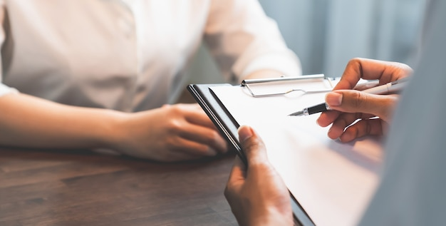 Businessman hand holding pen putting on the paper and draft contract with the customers.