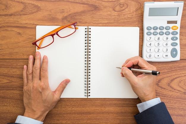 空白のノートブックとペンを持っているビジネスマンの手