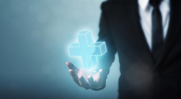 Бизнесмен рука держит знак плюс виртуальные средства, чтобы предложить положительное (например, преимущества, личностное развитие, социальная сеть)
