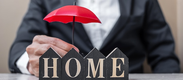 Businessman hand holding red umbrella cover wooden home model on table office.