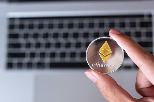 Рука бизнесмена, держащая монету криптовалюты silver ethereum (eth) над клавиатурой ноутбука, crypto - это цифровые деньги в сети блокчейн, использует технологии и онлайн-обмен в интернете.