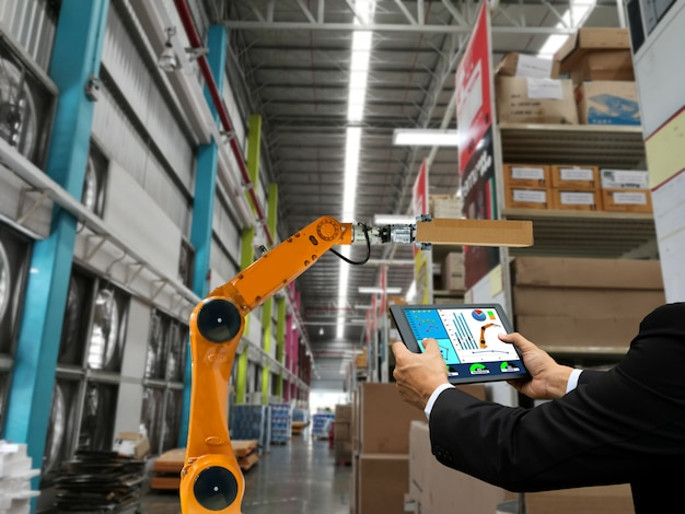 Businessman hand holding a tablet smart robot industry arm products storage factory and warehouse