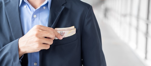 Businessman hand holding thai baht banknote stack.