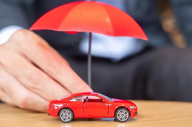 사업가 손을 테이블에 우산 덮개 또는 보호 빨간 자동차 장난감을 들고