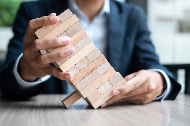 Businessman hand holding wooden block on the tower