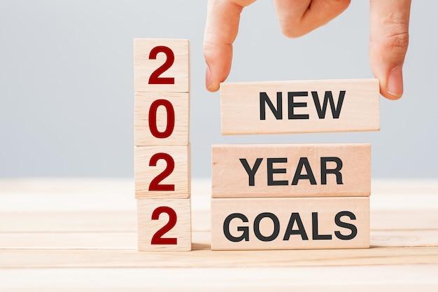 テーブルの背景にテキスト2022年新年の目標と木製のブロックを持っているビジネスマンの手。解決策、戦略、ソリューション、ビジネスおよび休日の概念