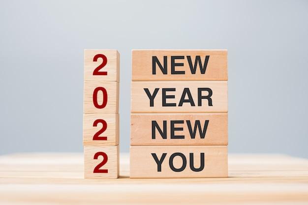 テーブルの背景にテキスト2022new year newyouと木製のブロックを保持しているビジネスマンの手。解決策、戦略、目標、ビジネスと休日の概念