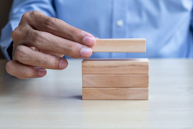 Businessman hand holding wooden building blocks on table