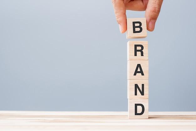 Рука бизнесмена держа деревянный блок куба с словом дела бренда на предпосылке таблицы. концепция маркетинга, рекламы и развития продуктов