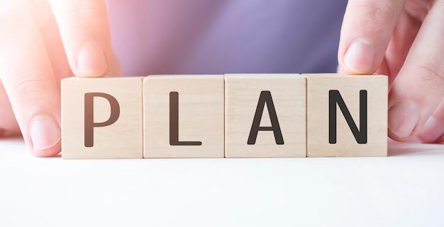テーブルの背景にplanビジネスワードと木製の立方体ブロックを持っているビジネスマン。ミッション、ビジョン、コアバリューのコンセプト