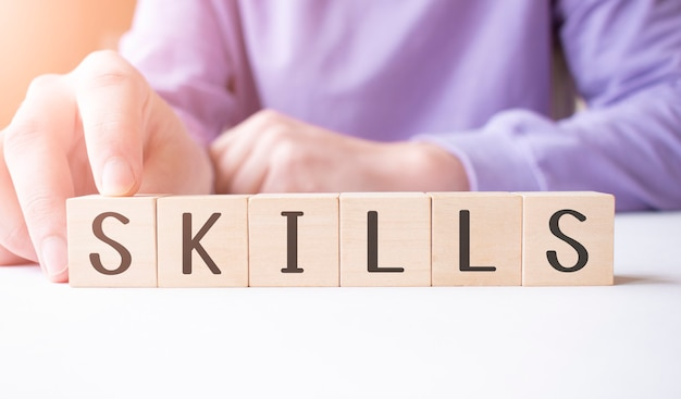 Рука бизнесмена держа деревянный блок куба словом дела навыка на фоне таблицы. концепция миссии, видения и основных ценностей
