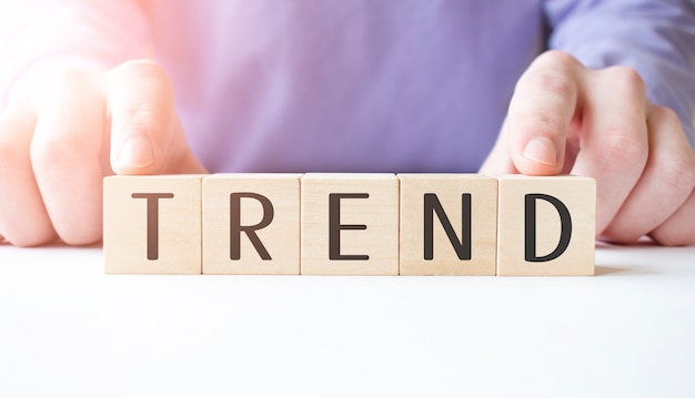 Бизнесмен рука деревянный кубик блок с бизнес-словом тренд на фоне таблицы. концепция миссии, видения и основных ценностей