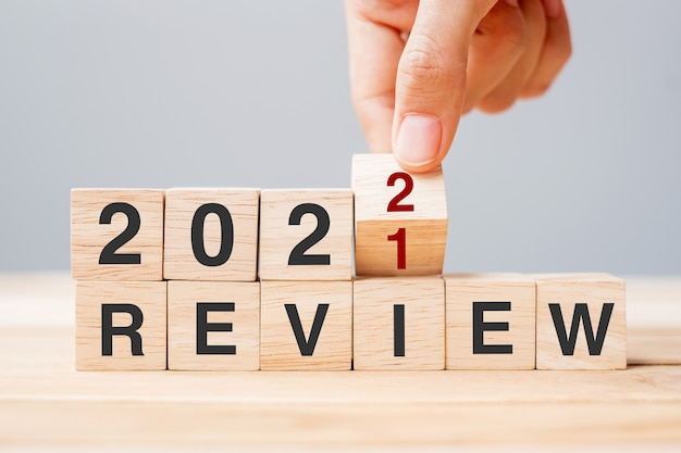 Businessman hand holding wooden cube and flip over block 2021 to 2022 review on table background. resolution, goal, change, start and new year holiday concepts