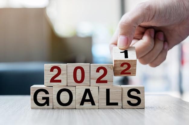 テーブルの背景にブロック2021年から2022年の目標の単語をめくって木製の立方体を持っているビジネスマンの手。解決策、戦略、ソリューション、目標、ビジネス、年末年始の概念