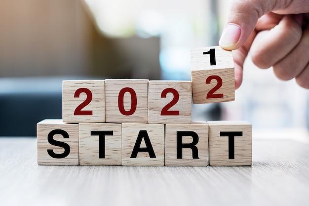 テーブルの背景にブロック2021から2022start単語をめくって木製の立方体を持っているビジネスマンの手。解決策、戦略、ソリューション、目標、ビジネス、年末年始の概念