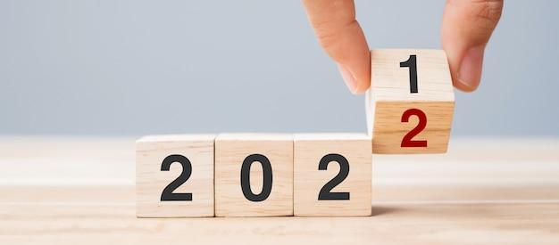 Рука бизнесмена держа деревянный куб с перевернутым текстом блока 2021-2022 на фоне таблицы. решение, стратегия, решение, цель, бизнес и концепции новогодних праздников