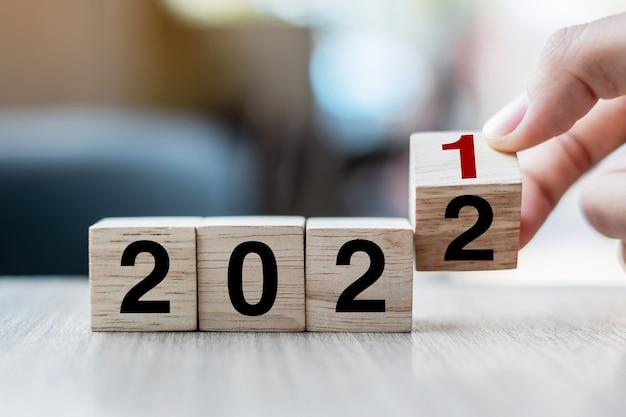 テーブルの背景にブロック2021から2022テキストをめくって木製の立方体を持っているビジネスマンの手。解決策、戦略、ソリューション、目標、ビジネス、年末年始の概念