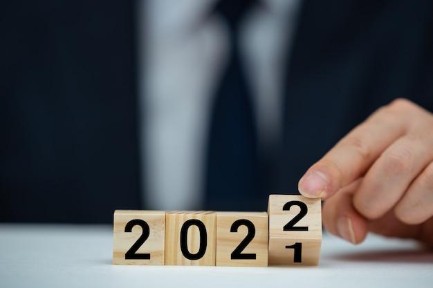 테이블 배경에 블록 2021에서 2022 텍스트 위로 플립이 있는 나무 큐브를 들고 있는 사업가 손.