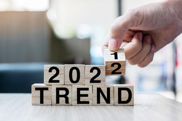 テーブルの背景にブロック2021から2022トレンドワードをめくって木製の立方体を持っているビジネスマンの手。解決策、戦略、ソリューション、目標、ビジネス、年末年始の概念